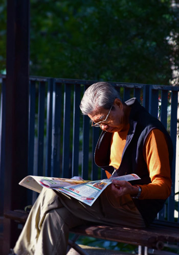 Man reading newspaper on bench